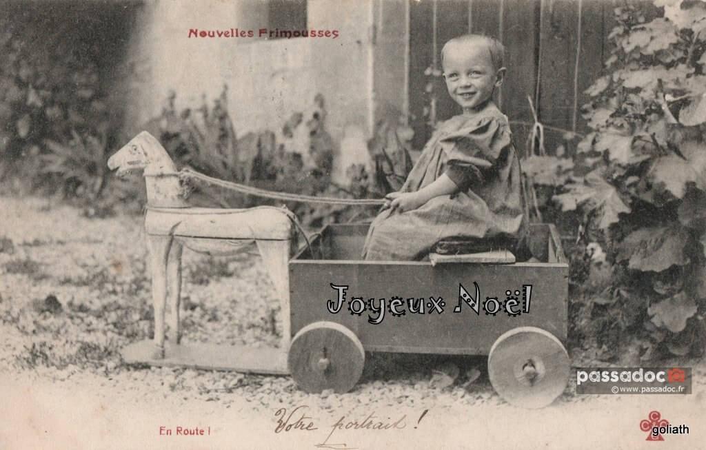 Un enfant dans un chariot en bois pour Noël