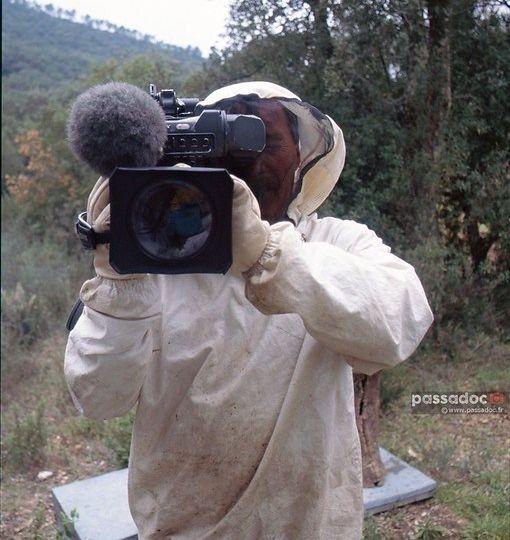 Un homme en tenue d apiculteur tenant une camera de television video - photo André Abbe.jpg